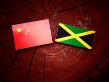 Κινεζική σημαία με την τζαμαϊκανή σημαία σε ένα κολόβωμα δέντρων Στοκ φωτογραφία με δικαίωμα ελεύθερης χρήσης