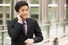 Κινεζικός επιχειρηματίας έξω από το γραφείο στο κινητό τηλέφωνο Στοκ Φωτογραφία