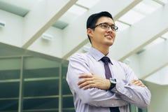 Κινεζικός επιχειρηματίας πορτρέτου που συλλογίζεται τον ουρανοξύστη γραφείων Στοκ Φωτογραφίες