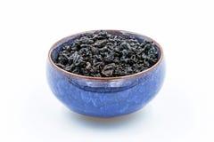 Κινεζικός μαύρος δεσμός Guan Yin τσαγιού Oolong σκούρο κόκκινο σε ένα μπλε κεραμικό κύπελλο Στοκ εικόνα με δικαίωμα ελεύθερης χρήσης
