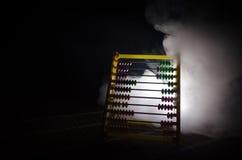Κινεζικός υπολογιστής με τις ζωηρόχρωμες χάντρες σκοτεινό υπόβαθρο καπνού πυρκαγιάς στο πορτοκαλί Φωτογραφία έννοιας της επιχείρη Στοκ Φωτογραφίες