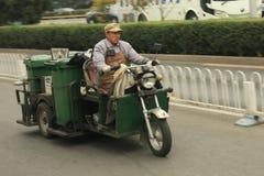 Κινεζικός janitor σε μια δροσερή πράσινη μοτοσικλέτα Στοκ εικόνα με δικαίωμα ελεύθερης χρήσης