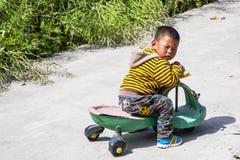 Κινεζικό αγόρι στο μηχανικό δίκυκλο Στοκ Εικόνες