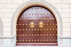 Κινεζικό εξόγκωμα applique bronz ζωικό επικεφαλής στις κόκκινες πόρτες πυλών Στοκ φωτογραφίες με δικαίωμα ελεύθερης χρήσης