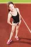 Κινεζικό θηλυκό athelete που τεντώνει στον αθλητικό τομέα Στοκ Εικόνες