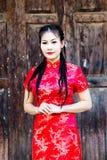 Κινεζικό κορίτσι στο παραδοσιακό κινέζικο cheongsam που ευλογεί Στοκ Φωτογραφία