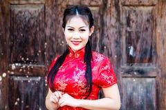 Κινεζικό κορίτσι στο παραδοσιακό κινέζικο cheongsam που ευλογεί Στοκ φωτογραφία με δικαίωμα ελεύθερης χρήσης