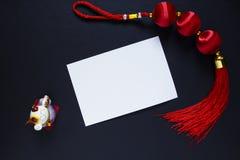 Κινεζικό νέο έτος dcer και κενή κάρτα εγγράφου στο Μαύρο Ασιατικό τυχερό ειδώλιο γατών neko κόμβων και maneki Στοκ Εικόνες