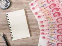 Κινεζικό νόμισμα τραπεζογραμματίων Yuan και υπολογιστής, σημειωματάριο, μολύβι στο ξύλινο υπόβαθρο Στοκ φωτογραφίες με δικαίωμα ελεύθερης χρήσης