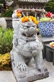 Κινεζικό πέτρινο άγαλμα λιονταριών με Marigolds τις γιρλάντες στο κεφάλι Στοκ φωτογραφία με δικαίωμα ελεύθερης χρήσης