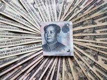 κινεζικό τραπεζογραμμάτιο δέκα yuan και του υποβάθρου με τους αμερικανικούς λογαριασμούς δολαρίων στοκ εικόνες