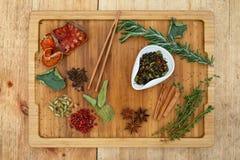 Κινεζικό τσάι μιγμάτων Oolong ξηρό σε ένα άσπρο κύπελλο Σε έναν ξύλινο πίνακα διεσπαρμένο πολλά συστατικά για το τσάι Στοκ Φωτογραφίες