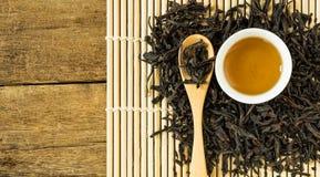 Κινεζικό τσάι στο άσπρο κεραμικό φλυτζάνι και ξηρά φύλλα τσαγιού στο ξύλινο κουτάλι Στοκ Φωτογραφίες