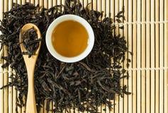 Κινεζικό τσάι στο άσπρο κεραμικό φλυτζάνι και ξηρά φύλλα τσαγιού στο ξύλινο κουτάλι Στοκ εικόνα με δικαίωμα ελεύθερης χρήσης