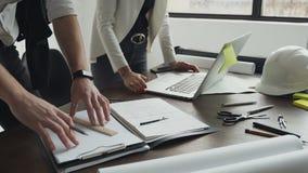Κινηματογράφηση σε πρώτο πλάνο Άτομο αρχιτεκτόνων που εργάζεται με το lap-top και τα σχεδιαγράμματα, επιθεώρηση μηχανικών στον ερ απόθεμα βίντεο