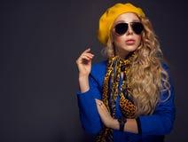 Κινηματογράφηση σε πρώτο πλάνο ένα κορίτσι κίτρινο beret και τη φθορά της τοποθέτησης γυαλιών ηλίου Στοκ Εικόνα