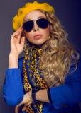Κινηματογράφηση σε πρώτο πλάνο ένα κορίτσι κίτρινο beret και τη φθορά της τοποθέτησης γυαλιών ηλίου Στοκ Φωτογραφίες
