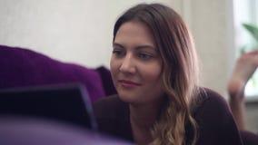 Κινηματογράφηση σε πρώτο πλάνο Ένα όμορφο νέο κορίτσι βρίσκεται στον καναπέ και απολαμβάνει μια ταμπλέτα που κινεί τα πόδια της H απόθεμα βίντεο