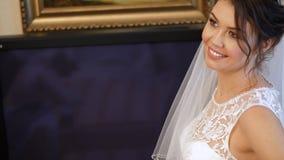 Κινηματογράφηση σε πρώτο πλάνο, αμοιβές νυφών η νύφη είναι ντυμένη για το γάμο πορτρέτο μιας όμορφης, χαμογελώντας νύφης, στο πέπ φιλμ μικρού μήκους