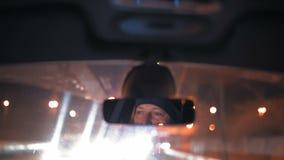 Κινηματογράφηση σε πρώτο πλάνο, αντανάκλαση των ατόμων στον οπισθοσκόπο καθρέφτη ενός αυτοκινήτου που οδηγά μέσω της πόλης νύχτας απόθεμα βίντεο