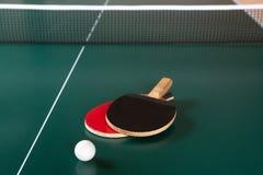 Δύο ρακέτες αντισφαίρισης και μια σφαίρα σε έναν πράσινο πίνακα αντισφαίριση καθαρή στοκ εικόνα με δικαίωμα ελεύθερης χρήσης