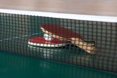 Δύο ρακέτες αντισφαίρισης και μια σφαίρα σε έναν πράσινο πίνακα αντισφαίριση καθαρή στοκ εικόνα