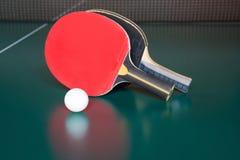 Δύο ρακέτες αντισφαίρισης και μια σφαίρα σε έναν πράσινο πίνακα αντισφαίριση καθαρή στοκ εικόνες με δικαίωμα ελεύθερης χρήσης