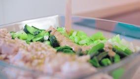 Κινηματογράφηση σε πρώτο πλάνο, σε αργή κίνηση, μαρούλι σε ένα κύπελλο σαλάτας γυαλιού του κοτόπουλου και πράσινες εγκαταστάσεις  απόθεμα βίντεο
