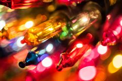 Κινηματογράφηση σε πρώτο πλάνο βολβών φω'των χριστουγεννιάτικων δέντρων στο bokeh ζωηρόχρωμο Στοκ Φωτογραφία