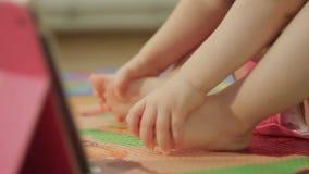 Κινηματογράφηση σε πρώτο πλάνο γυμνών ποδιών μιας μικρής συνεδρίασης κοριτσιών στο πάτωμα δίπλα σε μια ηλεκτρονική ταμπλέτα φιλμ μικρού μήκους