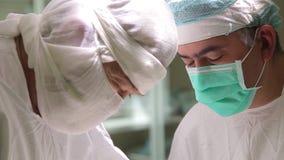 Κινηματογράφηση σε πρώτο πλάνο Δύο γιατροί χειρούργων στη προστατευτική ενδυμασία εκτελούν τη χειρουργική επέμβαση ογκολογίας απόθεμα βίντεο