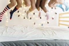 Κινηματογράφηση σε πρώτο πλάνο δύο ζευγαριών των ποδιών με τις κάλτσες που πηδούν στο κρεβάτι Στοκ Εικόνες