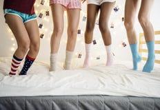 Κινηματογράφηση σε πρώτο πλάνο δύο ζευγαριών των ποδιών με τις κάλτσες που πηδούν στο κρεβάτι Στοκ Φωτογραφίες