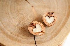 Κινηματογράφηση σε πρώτο πλάνο δύο μισά του ξύλου καρυδιάς στη μορφή της καρδιάς στο ξύλινο backgr Στοκ Φωτογραφία