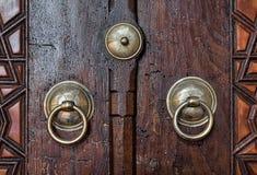 Κινηματογράφηση σε πρώτο πλάνο δύο παλαιών ρόπτρων πορτών χαλκού περίκομψων πέρα από μια ηλικίας ξύλινη πόρτα Στοκ Φωτογραφία