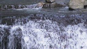 Κινηματογράφηση σε πρώτο πλάνο δύσκολος καταρράκτης βουνών Το ρεύμα νερού πέφτει γρήγορα κάτω και δημιουργεί τον άσπρο βράζοντας  φιλμ μικρού μήκους
