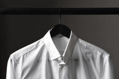 Κινηματογράφηση σε πρώτο πλάνο ενός άσπρου πουκάμισου φορεμάτων σε μια μαύρη κρεμάστρα Στοκ Εικόνες
