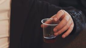 Κινηματογράφηση σε πρώτο πλάνο ενός ανθρώπινου χεριού που κρατά ένα πλαστικό μίας χρήσης γυαλί με το τσάι Στα δάχτυλα ενός ατόμου απόθεμα βίντεο