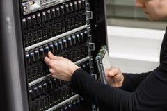 Κινηματογράφηση σε πρώτο πλάνο ενός αρσενικού τεχνικού ΤΠ που αναλύει το SAN σε Datacenter στοκ εικόνες