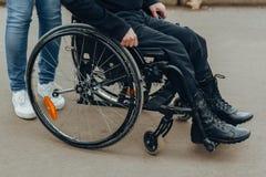 Κινηματογράφηση σε πρώτο πλάνο ενός αρσενικού χεριού σε μια ρόδα μιας αναπηρικής καρέκλας κατά τη διάρκεια ενός περιπάτου στο πάρ στοκ φωτογραφία με δικαίωμα ελεύθερης χρήσης
