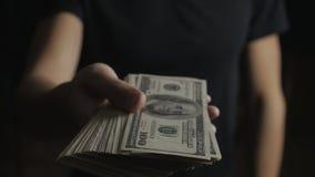 Κινηματογράφηση σε πρώτο πλάνο ενός ατόμου που δίνει ένα βαρέλι των λογαριασμών δολαρίων Η έννοια των αμοιβών φιλανθρωπία απόθεμα βίντεο