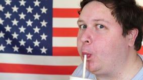 Κινηματογράφηση σε πρώτο πλάνο ενός ατόμου που πίνει ένα κοκτέιλ από το άχυρο μπροστά από τη αμερικανική σημαία απόθεμα βίντεο