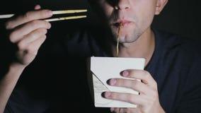 Κινηματογράφηση σε πρώτο πλάνο ενός ατόμου που τρώει τα νουντλς με chopsticks από ένα κιβώτιο Ευρωπαϊκά κινεζικά τρόφιμα κατανάλω φιλμ μικρού μήκους