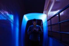 Κινηματογράφηση σε πρώτο πλάνο ενός ατόμου που χρησιμοποιεί το κινητό τηλέφωνο στο σκοτάδι με το μπλε μακροχρόνιο ε Στοκ Φωτογραφία