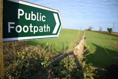 Κινηματογράφηση σε πρώτο πλάνο ενός δημόσιου σημαδιού μονοπατιών που λαμβάνεται με ένα ρηχό βάθος του τομέα στο Devon, UK στοκ εικόνες