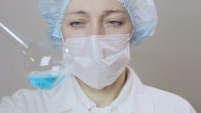 Κινηματογράφηση σε πρώτο πλάνο ενός θηλυκού γιατρού επιστημόνων που αναλύει τα κύτταρα ενός ρευστού ιού σε ένα επαγγελματικό εργα φιλμ μικρού μήκους