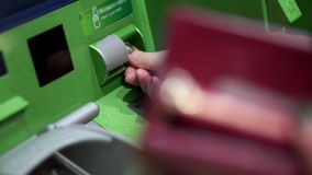 Κινηματογράφηση σε πρώτο πλάνο ενός θηλυκού χεριού που παρεμβάλλει μια πιστωτική κάρτα στο ATM εκλεκτική εστίαση, φιλμ μικρού μήκους