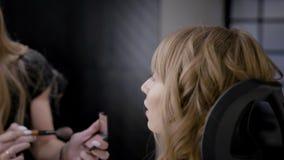 Κινηματογράφηση σε πρώτο πλάνο ενός καλλιτέχνη makeup που κάνει ένα επαγγελματικό makeup στο όμορφο ξανθό κορίτσι, makeup για τις απόθεμα βίντεο