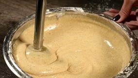 Κινηματογράφηση σε πρώτο πλάνο ενός κοριτσιού ζύμης στην κουζίνα σε ένα κύπελλο μετάλλων με ένα μπλέντερ που κτυπά τη ζύμη για το απόθεμα βίντεο