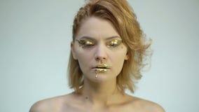 Κινηματογράφηση σε πρώτο πλάνο ενός κοριτσιού με μια χρυσή σύνθεση που ανοίγει και κλείνει τα μάτια της σε ένα άσπρο υπόβαθρο ένν φιλμ μικρού μήκους